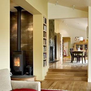 Modelo de biblioteca en casa contemporánea con paredes beige y estufa de leña