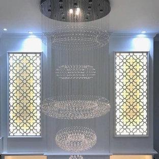 他の地域の中サイズのトロピカルスタイルのおしゃれなリビングロフト (ミュージックルーム、白い壁、セラミックタイルの床、壁掛け型テレビ、白い床) の写真