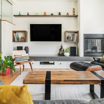 Inspiration for a mid-sized contemporary open concept medium tone wood floor and brown floor living room remodel in Seattle with white walls, a standard fireplace, a metal fireplace and a wall-mounted tv