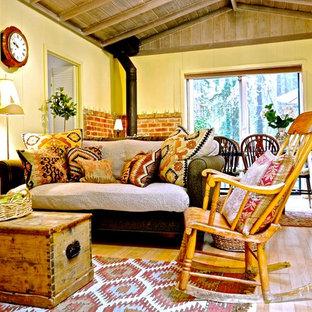Foto de salón abierto, romántico, de tamaño medio, con paredes beige, suelo de madera clara, estufa de leña y televisor retractable