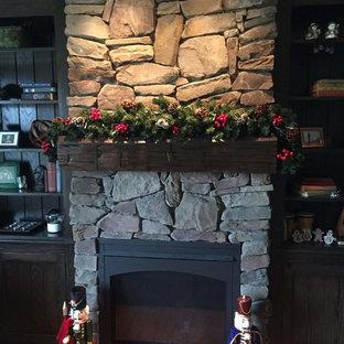 トロントの中くらいのラスティックスタイルのおしゃれなLDK (グレーの壁、無垢フローリング、標準型暖炉、石材の暖炉まわり、テレビなし、オレンジの床) の写真