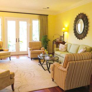 Foto di un soggiorno tradizionale di medie dimensioni e chiuso con pareti gialle, pavimento in legno massello medio, camino classico, sala formale, cornice del camino in pietra e nessuna TV