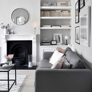 Cette photo montre un salon scandinave de taille moyenne et fermé avec un mur gris, un sol en bois clair, une cheminée standard, un manteau de cheminée en bois, un téléviseur indépendant et un sol beige.