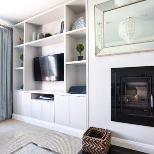 Diseño de biblioteca en casa cerrada, actual, de tamaño medio, con paredes grises, moqueta, estufa de leña, pared multimedia y suelo beige