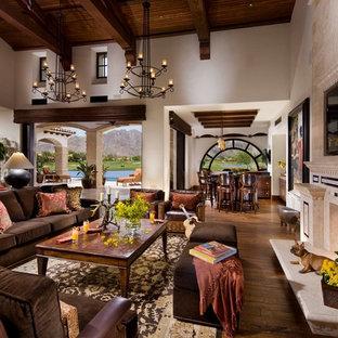 Exempel på ett medelhavsstil allrum med öppen planlösning, med beige väggar, mellanmörkt trägolv, en standard öppen spis och en spiselkrans i sten