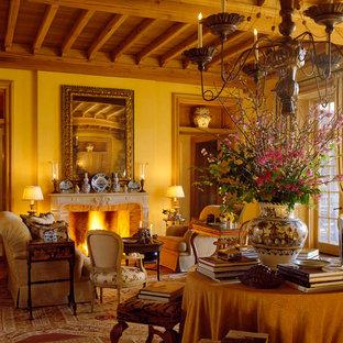 ダラスの地中海スタイルのおしゃれな独立型リビング (フォーマル、黄色い壁、標準型暖炉、石材の暖炉まわり、テレビなし) の写真