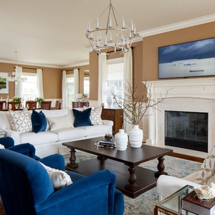 This is an example of a large traditional open plan living room in New York with a standard fireplace, a wall mounted tv, brown floors, brown walls, dark hardwood flooring and a stone fireplace surround.