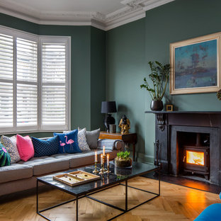Inspiration for a traditional living room in London with green walls, medium hardwood flooring, a wood burning stove, a stone fireplace surround and brown floors.