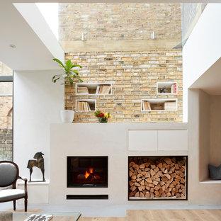 ロンドンの小さいコンテンポラリースタイルのおしゃれなLDK (白い壁、淡色無垢フローリング、漆喰の暖炉まわり、テレビなし) の写真