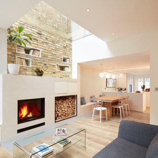ロンドンの小さいコンテンポラリースタイルのおしゃれなLDK (白い壁、淡色無垢フローリング、漆喰の暖炉まわり、テレビなし、標準型暖炉) の写真