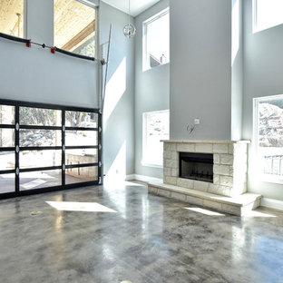 オースティンの大きいインダストリアルスタイルのおしゃれな独立型リビング (フォーマル、グレーの壁、コンクリートの床、標準型暖炉、石材の暖炉まわり、テレビなし、茶色い床) の写真