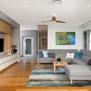 Large contemporary open concept living room in Brisbane with white walls, medium hardwood floors, a built-in media wall, brown floor, exposed beam and no fireplace.