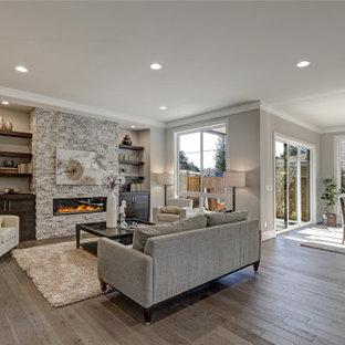 Offenes Klassisches Wohnzimmer mit grauer Wandfarbe, dunklem Holzboden, Gaskamin, Kaminumrandung aus gestapelten Steinen und braunem Boden in Orange County