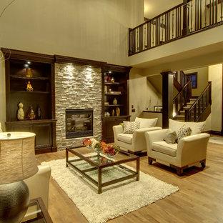 カルガリーの大きいトランジショナルスタイルのおしゃれなLDK (ベージュの壁、無垢フローリング、標準型暖炉、石材の暖炉まわり) の写真