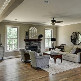 Immagine di un soggiorno american style di medie dimensioni e aperto con pareti grigie, pavimento in legno massello medio, camino classico e cornice del camino in pietra