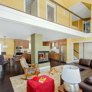 Immagine di un grande soggiorno tradizionale aperto con pareti gialle, parquet scuro, camino bifacciale, cornice del camino in metallo, nessuna TV e pavimento marrone