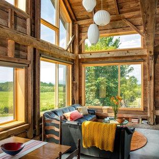 Diseño de salón para visitas abierto, rural, de tamaño medio, sin chimenea y televisor, con paredes marrones, suelo de cemento y suelo gris