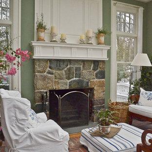 Cette photo montre un salon chic de taille moyenne et ouvert avec une salle de réception, un mur vert, un sol en brique, une cheminée standard, un manteau de cheminée en pierre et un sol gris.