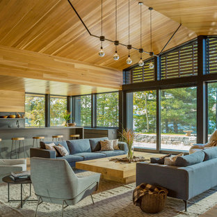 Photo of an expansive rustic open plan living room in Burlington with medium hardwood flooring, brown floors, no tv, brown walls, a two-sided fireplace and a metal fireplace surround.