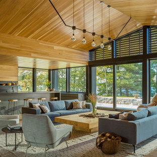 Imagen de salón abierto, rústico, extra grande, sin televisor, con suelo de madera en tonos medios, suelo marrón, paredes marrones, chimenea de doble cara y marco de chimenea de metal