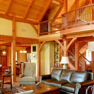 Idee per un grande soggiorno stile rurale con pareti gialle, pavimento in legno massello medio, camino classico, cornice del camino in pietra e nessuna TV