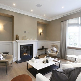 Inspiration for a medium sized traditional enclosed living room in London with beige walls, light hardwood flooring, a standard fireplace and beige floors.
