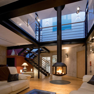 Large trendy open concept and formal medium tone wood floor and brown floor living room photo in Boston with black walls, a hanging fireplace, a plaster fireplace and no tv