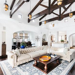 Ejemplo de salón con barra de bar abierto, mediterráneo, grande, con paredes blancas, suelo de madera oscura, chimenea tradicional y suelo marrón