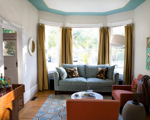 gold curtains living room. example of a mid-sized eclectic enclosed medium tone wood floor living room design in gold curtains n