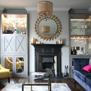 Foto di un piccolo soggiorno tradizionale chiuso con pareti grigie, parquet scuro, camino classico, cornice del camino in metallo e pavimento marrone