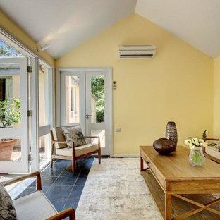 Foto di un piccolo soggiorno country chiuso con pareti gialle, pavimento in ardesia e pavimento grigio