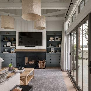 Idées déco pour un salon campagne avec un mur blanc, un sol en bois clair, une cheminée standard, un téléviseur fixé au mur, un sol marron, un manteau de cheminée en métal et du lambris de bois.