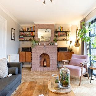 Exempel på ett klassiskt vardagsrum, med rosa väggar, en standard öppen spis, en spiselkrans i tegelsten, ljust trägolv och beiget golv