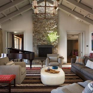 Idées déco pour un salon campagne avec un mur blanc, un sol en bois brun, une cheminée standard, un manteau de cheminée en pierre et un sol marron.