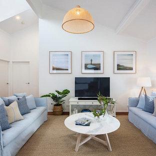 サンシャインコーストの大きいビーチスタイルのおしゃれなリビングロフト (白い壁、据え置き型テレビ、茶色い床、濃色無垢フローリング) の写真