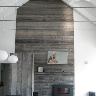 Esempio di un soggiorno contemporaneo di medie dimensioni con pareti bianche, pavimento in legno massello medio, camino sospeso, cornice del camino in metallo, nessuna TV e pavimento grigio