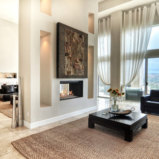 Example of a large minimalist formal and enclosed travertine floor and beige floor living room design in Orange County with white walls, a two-sided fireplace, no tv and a plaster fireplace