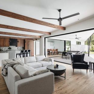 フェニックスのミッドセンチュリースタイルのおしゃれなLDK (白い壁、無垢フローリング、横長型暖炉、漆喰の暖炉まわり、壁掛け型テレビ、表し梁) の写真