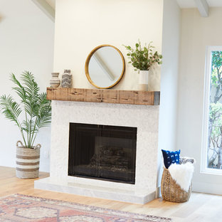 This is an example of a large country formal open concept living room in San Diego with white walls, light hardwood floors, a standard fireplace, a tile fireplace surround and beige floor.