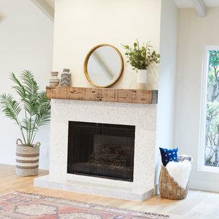 Foto di un grande soggiorno country aperto con pareti bianche, sala formale, parquet chiaro, camino classico, cornice del camino piastrellata e pavimento beige