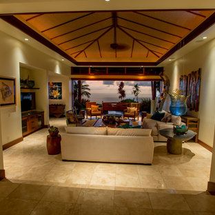 This is an example of a large world-inspired open plan living room in Hawaii with white walls, limestone flooring and a built-in media unit.