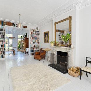 Immagine di un soggiorno bohémian di medie dimensioni e chiuso con pavimento in legno verniciato, camino classico, pavimento bianco e pareti bianche