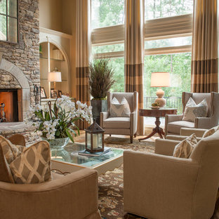 Inspiration for a mid-sized timeless formal and open concept medium tone wood floor and brown floor living room remodel in Atlanta with a standard fireplace, a stone fireplace, beige walls and no tv