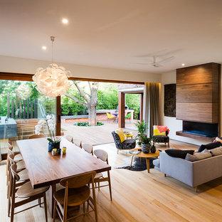 Imagen de salón para visitas abierto, contemporáneo, sin televisor, con suelo de madera en tonos medios, chimenea lineal, marco de chimenea de madera y paredes beige