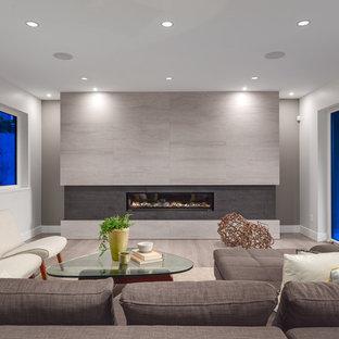 Immagine di un grande soggiorno minimal aperto con pareti grigie, camino lineare Ribbon, cornice del camino piastrellata, nessuna TV e parquet chiaro