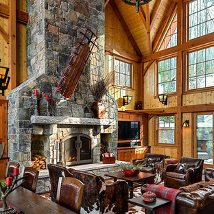 Inspiration for a large rustic open plan living room in Burlington with brown walls, dark hardwood flooring, a standard fireplace, a stone fireplace surround and a freestanding tv.