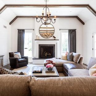Immagine di un soggiorno country di medie dimensioni e stile loft con pareti bianche, parquet scuro, camino classico, TV a parete e cornice del camino in cemento
