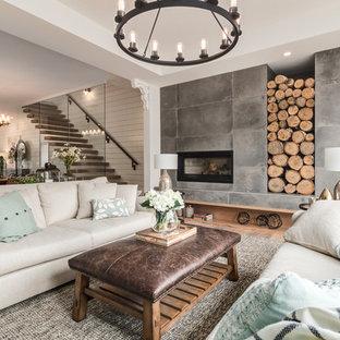 Foto di un grande soggiorno country aperto con sala formale, pareti bianche, parquet chiaro, camino classico, pavimento beige, cornice del camino in cemento e nessuna TV