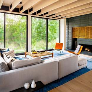 Inspiration for a contemporary medium tone wood floor and brown floor living room remodel in New York with a standard fireplace and a concealed tv