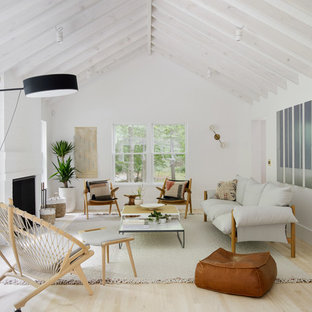 Photo of a scandinavian enclosed living room in New York with white walls, light hardwood flooring and a standard fireplace.